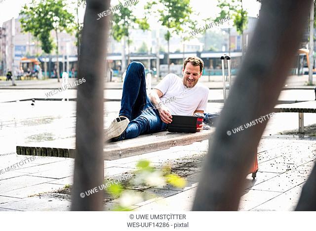 Smiling man lying on bench using tablet