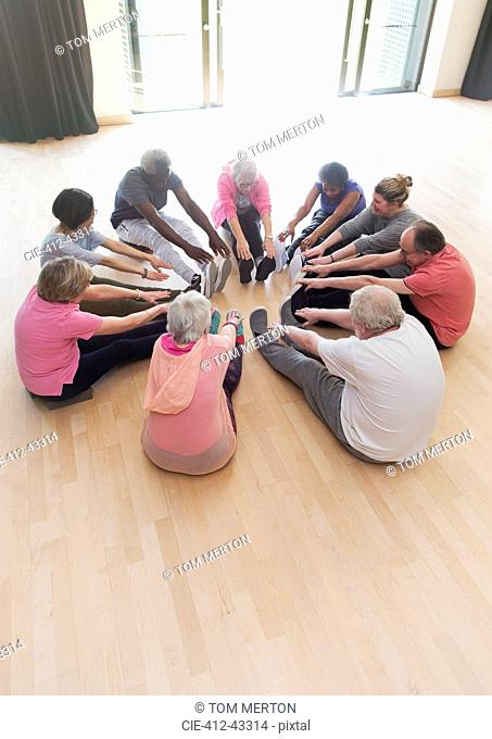 Active seniors stretching legs in circle