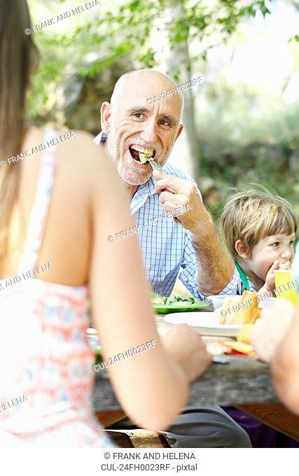 Older man eating at family picnic
