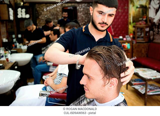 Hairdresser in barbershop cutting young mans hair