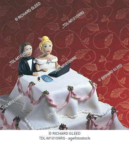 A Wedding Cake, bride and groom sitting at a desk together