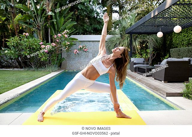 Mid-Adult Woman in Yoga Pose, Outdoor with Swimming Pool in Background