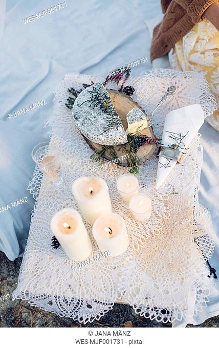 Glass of champagne, plate with soft cheese and lighted candles on lace