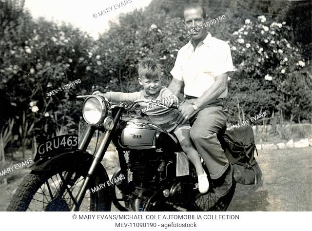 Father & young son pose for a photograph on a vintage BSA motorcycle in the back garden in the 1950s