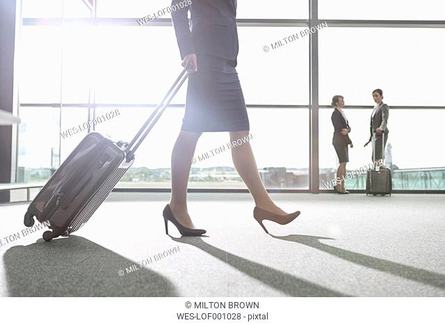Flight attentdants and businesswoman at a window at the aiport