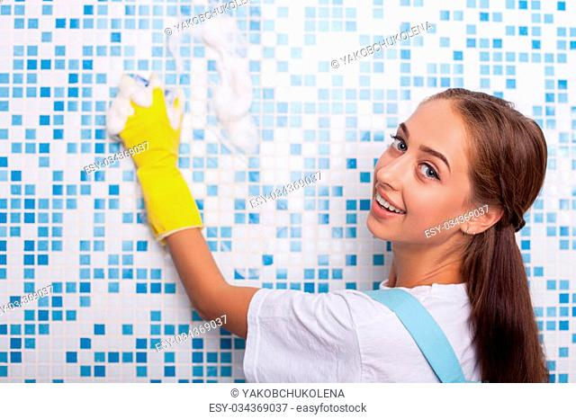 Attractive female cleaner is doing clean-up in bathroom. She is scrubbing a tiled wall with a sponge. The woman is looking at the camera and smiling