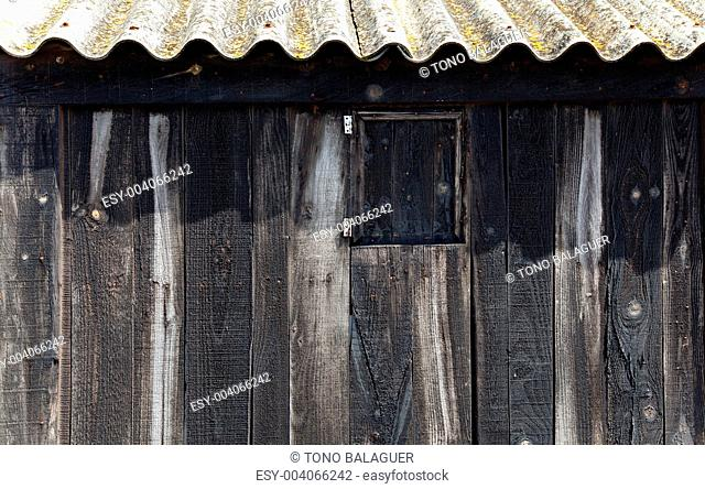Aged black wood with wavy roof in balearic beach