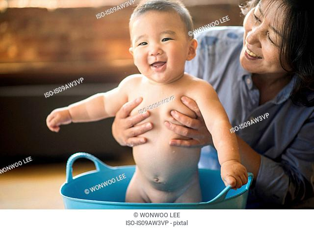 Grandmother bathing grandson in tub