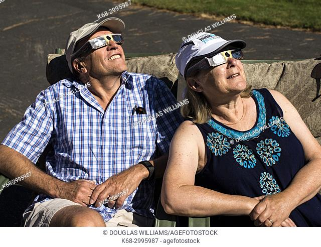 Couple looking at solar eclipse with protective glasses
