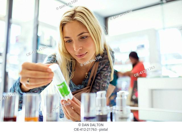 Woman examining skincare product in drugstore