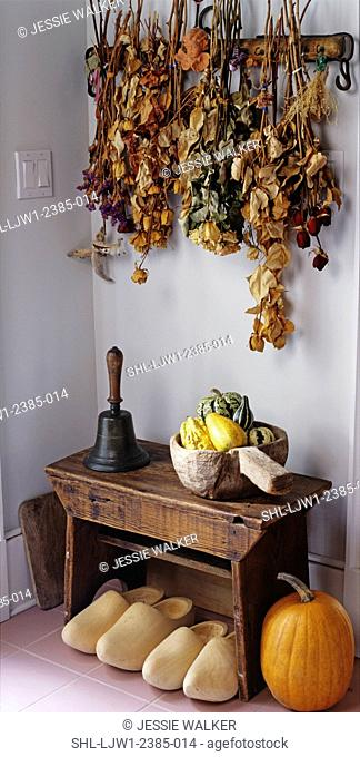 entry ways: area decorated with dried flowers hanging from wall, small bench with old hand bell, wooden bowl filled with gourds, dutch shoes