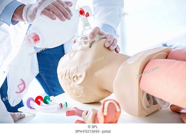 Doctor practising bag-valve-mask ventilation on dummy