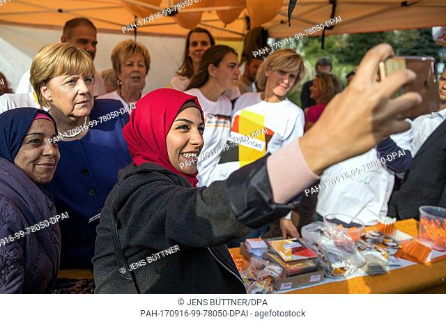 Ghalia Badr, who fled from Damaskus takes a selfie with the German Chancellor Angela Merkel (CDU) at the citizen festival in Stralsund, Germany