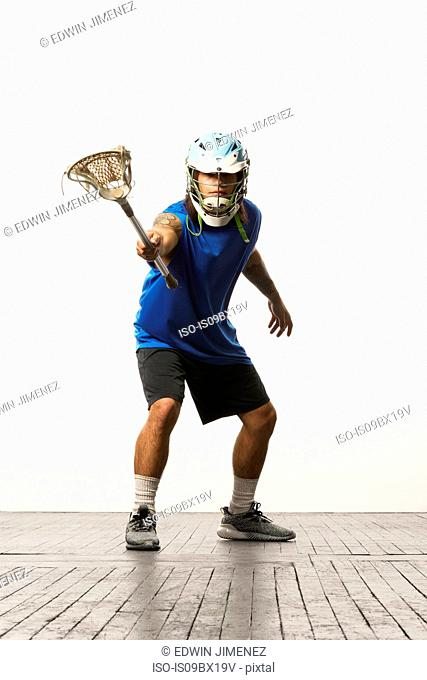 Man modelling lacrosse helmet and stick