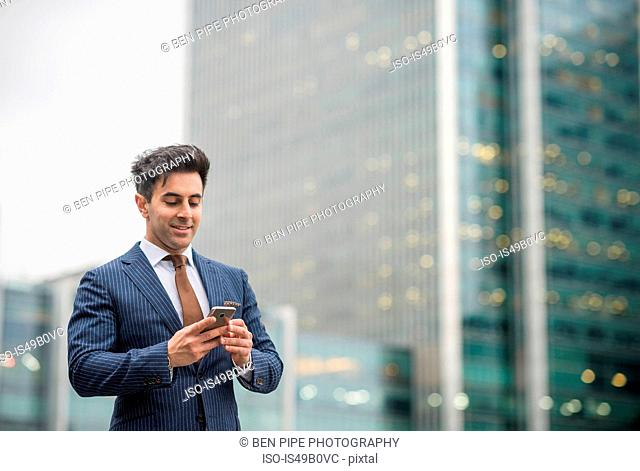Businessman using mobile phone, Canary Wharf, London, UK