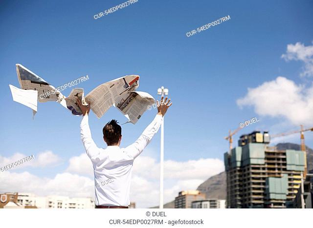 Businessman throwing newspaper in air