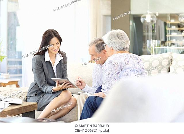 Financial advisor using tablet computer with clients