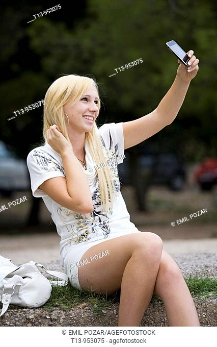 Fancy young woman taking photo of herself with a cellular phone