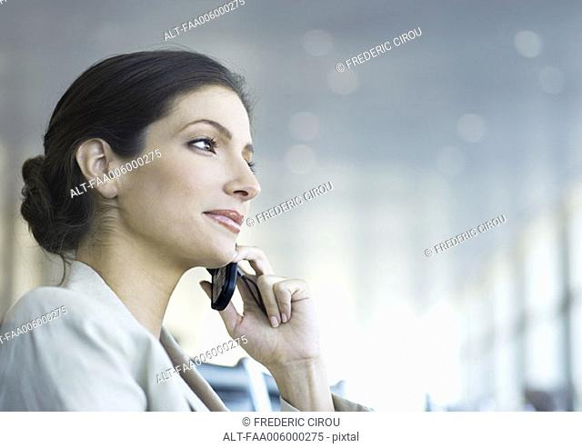 Businesswoman using cell phone, low angle view