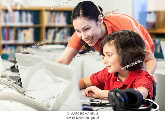 Teacher and student using laptop in library