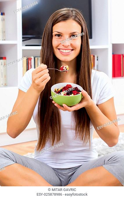 Happy young woman eating cereal muesli with fruits in bowl at home. Healthy Food and Dieting concept