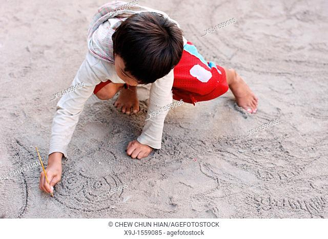 Children drawing on top of the sand floor in Mabul Island, Mabul, Sabah, Malaysia, Borneo