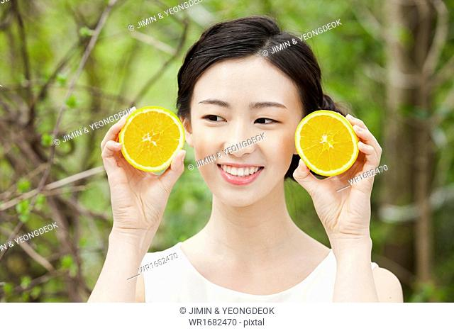 a woman holding an orange in the nature