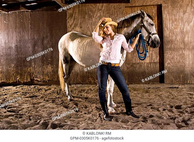 Portrait of young cowgirl with white Gelding horse in stable