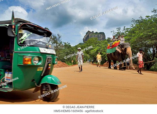 Sri Lanka, North-Central Province, Polonnaruwa District, Sigiriya, Tuk-tuk, delivery tricycle and an elephant on a road with the Rock of the Lion in background