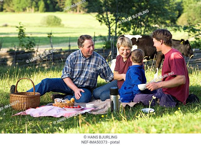 A farmer family taking a break in the grass, Sweden