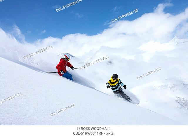 Skier and snowboarder on snowy slope
