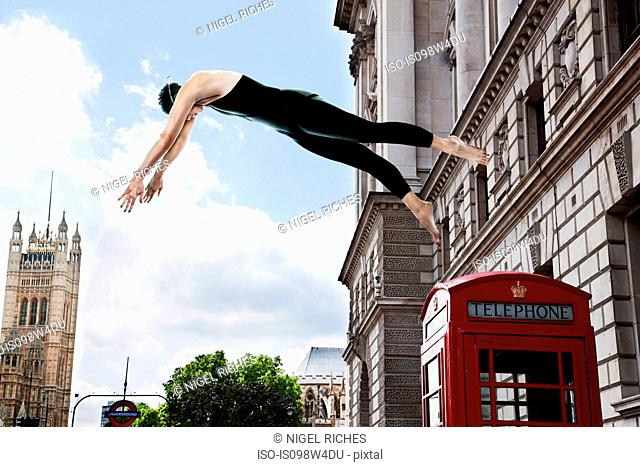 Swimmer diving from red telephone box, London, England