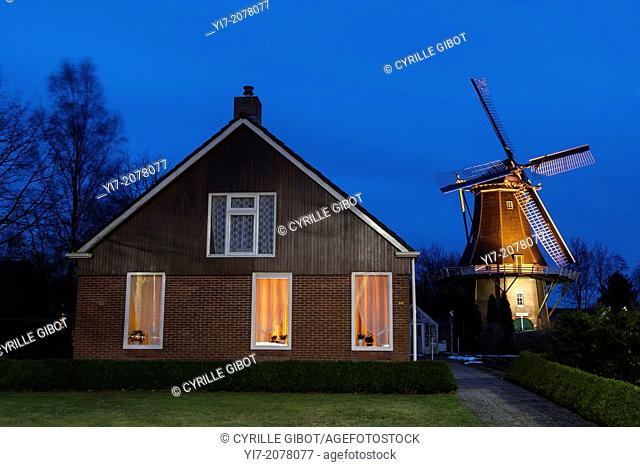 House and windmill at dusk, Vriescheloo, Groningen province, Netherlands