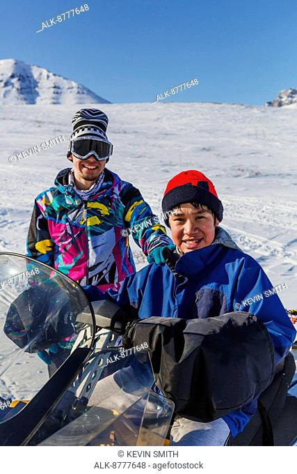 Portrait of two Alaskan native youths wearing snowboarding cloths sitting on a snowmachine, Anaktuvuk Pass, Gates of the Arctic National Park, Brooks Range