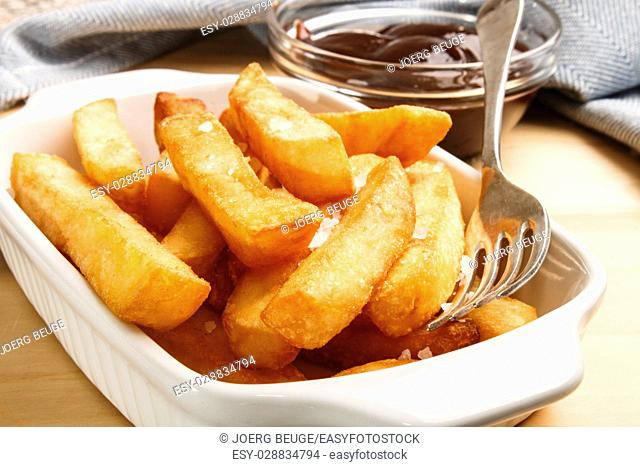 french fries with british brown sauce and fork in a bowl