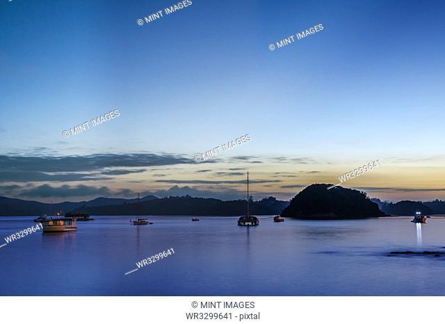Boats sailing in bay at dawn, Bay of Islands, New Zealand