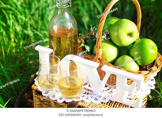 Apple drink and basket with green apples outdoors