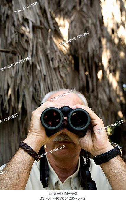 Balding Eldery Man With Moustache Looking Through Binoculars
