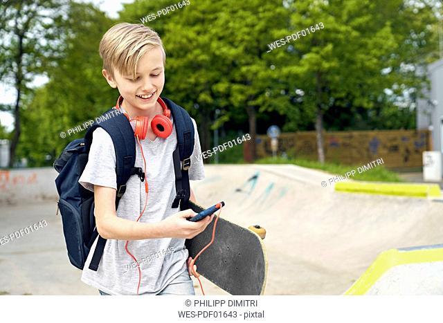 Boy with headphones, skateboard and school bag using smartphone