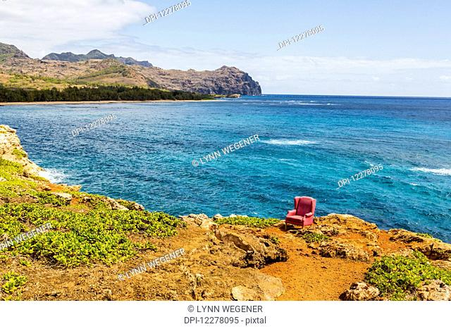 View of a red stuffed arm chair placed on a cliff edge; Poipu, Kauai, Hawaii, United States of America