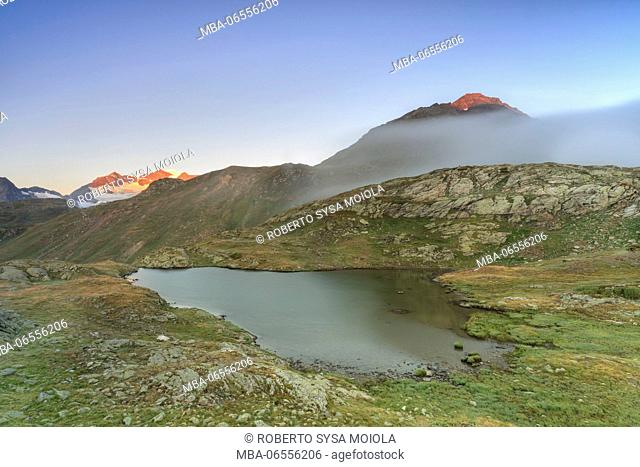 Mist at sunrise on the alpine lake in the background the snowy peaks Minor Valley Alta Valtellina Livigno Italy Europe