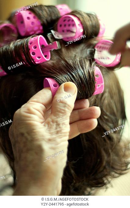 Old woman putting curlers another woman