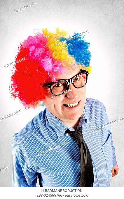 Funny businessman with clown wig on gray background
