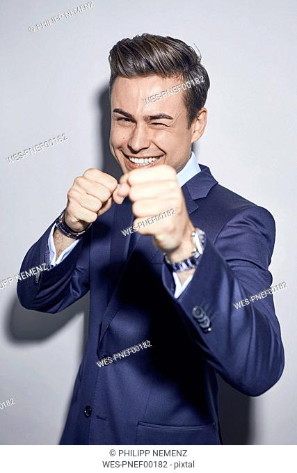 Portrait of laughing young businessman boxing