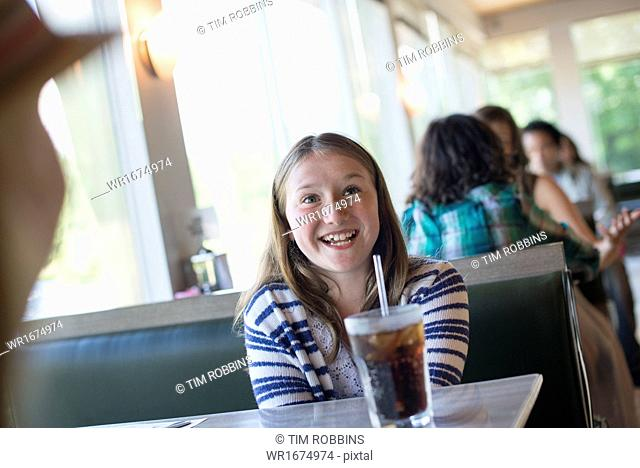 A child seated at a diner with a large cold drink in a glass with a straw