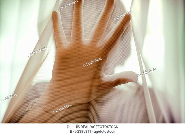 Closeup of a hand in front of face, of a woman, in a position to stop behind a transparent curtain