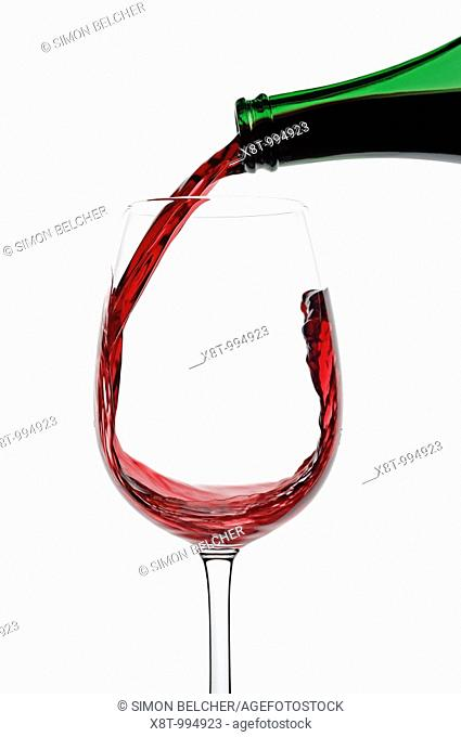 Red Wine Being Poured into a Glass Against a White Background, Close Up