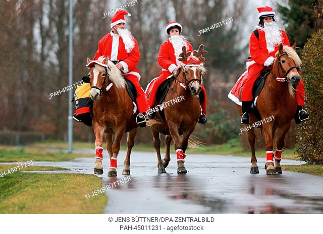 Equestrians dressed as Santas distribute Christmas gifts to seniors with an illuminated and decorated carriage on the island of Ummanz off the west coast of the...