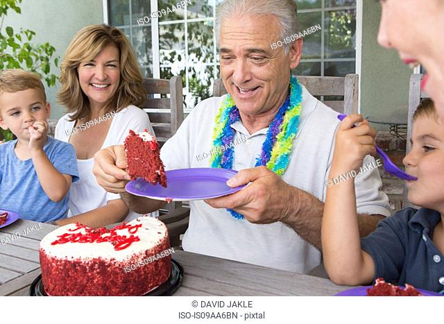 Senior man serving slice of birthday cake at party with family