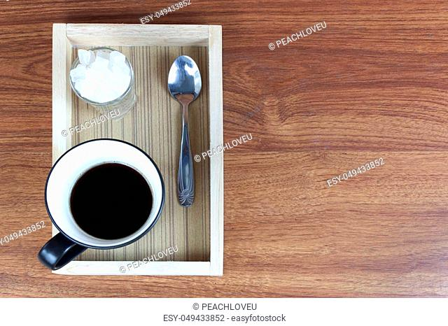 Black Coffee and rock sugar in wood tray on wood table